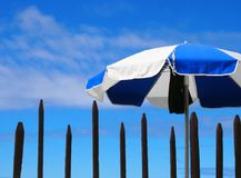 Beach umbrella against a cloudy sky with wooden spiked fence stock photos