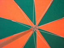 Beach umbrella. Background green and orange Royalty Free Stock Image