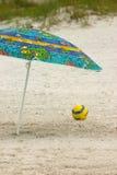 Beach umbrella and ball. A colorful beach umbrella and a yellow ball on a sandy beach Stock Photos