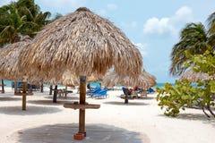 Beach umbrella and beach chairs on Palm Beach at Aruba island in. At the beach on the tropical island Aruba in the Caribbean Sea Stock Photos