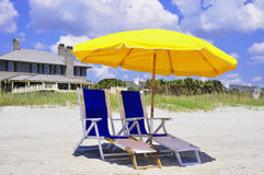Beach Umbrella and Beach Chairs. Two beach chairs and umbrella on the sand waiting for guest to relax and enjoy the seashore Stock Images