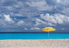 Beach umbrella and Beautiful beach Myrtos with clear turquoise water on a sunny day in the Ionian Sea on the island of Kefalonia royalty free stock photos