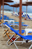 Beach umbrella and beds. Sun loungers and beach umbrella blue water sea royalty free stock images