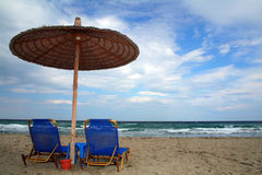 Beach umbrella and beds. Two sun loungers and beach umbrella blue water sea waves royalty free stock photos