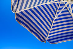 Beach umbrella with blue and white stripes Stock Photos