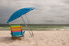 Beach Umbrella and Chair. Colorful beach umbrella, chair and fishing rods on golden sandy beach with sea in background royalty free stock images