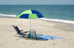 Beach Umbrella and Chair by Ocean. A blue and green beach umbrella with beach chair, on the beach by the ocean, horizontal with copy space Royalty Free Stock Photography