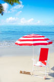 Beach umbrella and chair by the ocean Royalty Free Stock Image