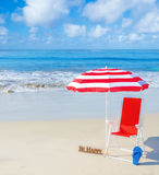 Beach umbrella and chair by the ocean Stock Photo