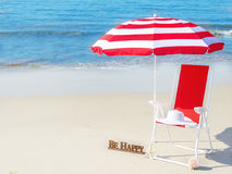 Beach umbrella and chair by the ocean Stock Photography