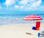 Beach umbrella and chair by the ocean Stock Photos