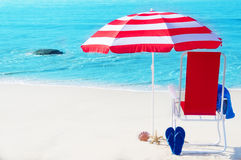 Beach umbrella and chair by the ocean Royalty Free Stock Images