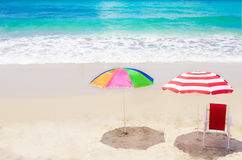 Beach umbrella and chair by the ocean Stock Images