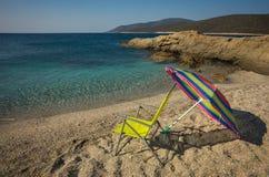 Beach umbrella and chair on a sandy beach Zastani, Evia Stock Photo