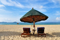 Beach umbrella and chairs. Scenic view of sun loungers and umbrella on sandy beach under cloudscape, Yalong Bay, Sanya City, Hainan Province, China Royalty Free Stock Photos