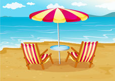 A beach umbrella with chairs at the seashore Stock Photo