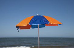 Beach Umbrella Colourfull Against Blue Sky and Sea. A single orange and blue beach umbrella contrasted against a clear blue sky down at the beach Royalty Free Stock Photography