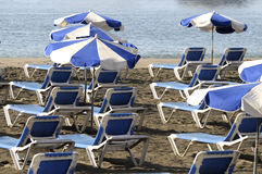 Beach umbrella with deckchairs Stock Images