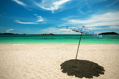 Beach umbrella with emerald sea on a sunny day, island in backgr Royalty Free Stock Photos