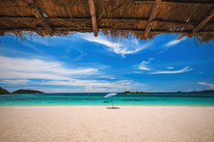 Beach umbrella with emerald sea on a sunny day, island in backgr Stock Image