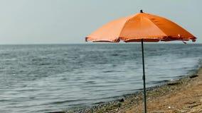 Beach umbrella on an empty beach. Orange beach umbrella on an empty beach stock video footage