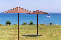 Beach umbrella on green grass at the sea in Cyprus. A boat at the horizon Stock Images