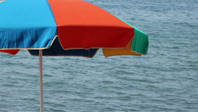 Beach umbrella on the left. A colorful beach umbrella on the wind with sea waves on the background and some copy space on the right stock video