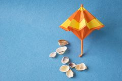 Beach umbrella model and sea shells on blue background. Tropical sea vacation and holiday. Beach umbrella model and sea shells on blue background with copy Stock Photography