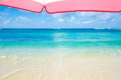 Beach umbrella next to ocean background Stock Photo