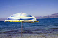 Beach umbrella by ocean. Single beach umbrella by side of blue ocean Stock Photo