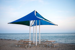 Beach Umbrella and Picnic Tables. Blue and Green Beach Umbrella and Four Picnic Tables set on a Waterfront Background, with a Lakeside view and on top of Sand Stock Photography