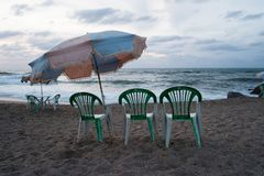 Beach umbrella and plastic chairs on the beach in bad weather stock photo