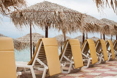 Beach umbrella and plastic deck chairs on the beach,Greek , pefk Royalty Free Stock Photography