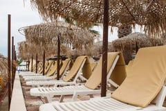 Beach umbrella and plastic deck chairs on the beach,Greek , pefk Stock Photos