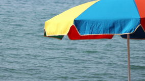 Beach umbrella on the right. A colored beach umbrella on the wind with sea waves on the background and some copy space on the left stock footage