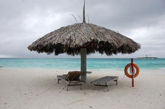 Beach umbrella and sun lounger with lifebuoy at Maldives Stock Images