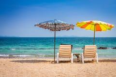 Beach umbrella and sunbath seats and side table are on sand beach Royalty Free Stock Photos