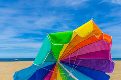 Beach umbrella with sunning blue sky background. Rainbow colour beach umbrella with sunning blue sky background Stock Photo
