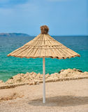 Beach umbrella on a sunny day on the coast of tropical island Royalty Free Stock Photo