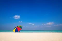 Beach umbrella on a sunny day, sea in background Stock Photos