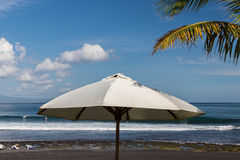 Beach umbrella on a sunny day, sea in background. Tropical beach with black sand. Beautiful sky. Paradise island Bali.  Royalty Free Stock Photo