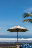 Beach umbrella on a sunny day, sea in background. Tropical beach with black sand. Beautiful sky. Paradise island Bali Royalty Free Stock Image