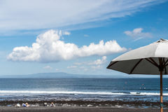 Beach umbrella on a sunny day, sea in background. Tropical beach with black sand. Beautiful sky. Paradise island Bali Royalty Free Stock Photo