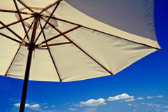Beach umbrella on a sunny holiday day. A holiday-inspired shot of a beach umbrella on a bright blue sky Royalty Free Stock Photo