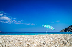 Beach umbrella on sunny Myrtos beach, the ionian sea in backgrou Stock Photos