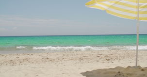 Beach umbrella on a sunny tropical beach. With golden sand and an azure blue ocean conceptual of a summer vacation and travel stock footage