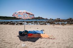 Beach umbrella and towel on the sand Royalty Free Stock Images