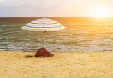 Beach umbrella. Towels and sandals under colorful beach umbrella inside green ocean at sunrise Stock Photo