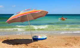 Beach umbrella and toy boat at sea Stock Images