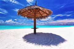 Beach umbrella on white sand next to lagoon Stock Image
